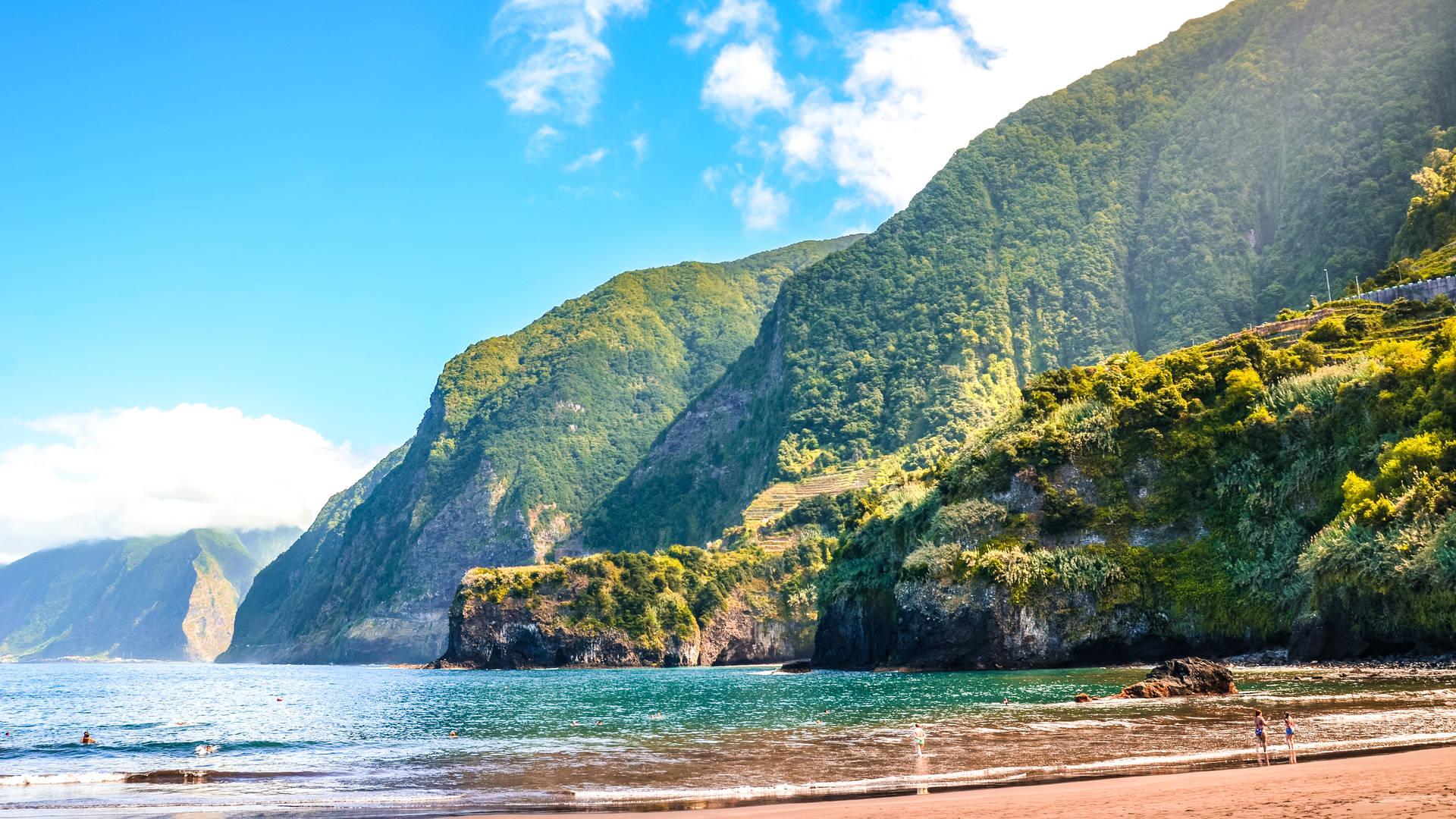 Het strand Seixal op Madeira. Zwart strand omgeven door groene natuur